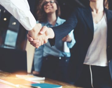 Business woman shaking hands with another business person