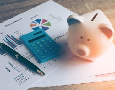 A pen, a calculator and a piggy bank on top of financial papers